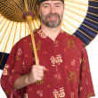 Man in Chinese dress holding an umbrella - Stock Photo