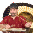 European in chinese costume smokes pipe — Stock Photo