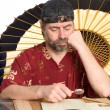 Man in chinese costume reads — Stock Photo