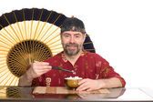 European in chinese attire eating rice — Foto Stock