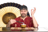 European in chinese attire eating rice — Stock Photo
