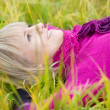 Beautiful girl lying on fall grass — Stock Photo
