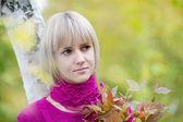 красивая блондинка в осенней листвой — Стоковое фото