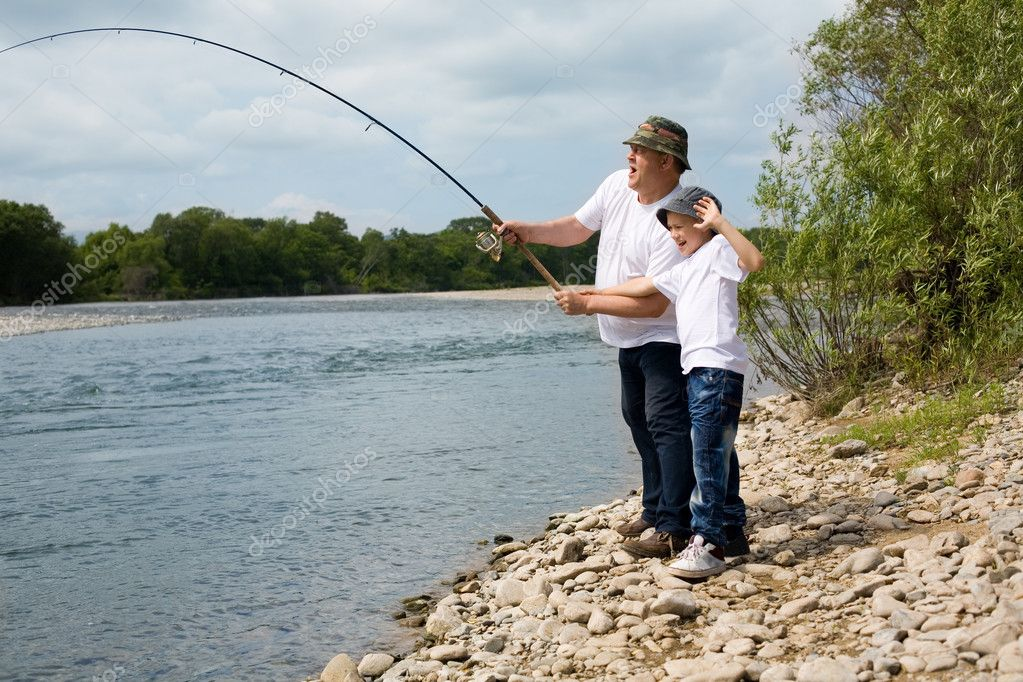 Grandfather and grandson fishing on the river. — Stock Photo #11657316