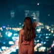 Woman watching the city at night — Stock Photo
