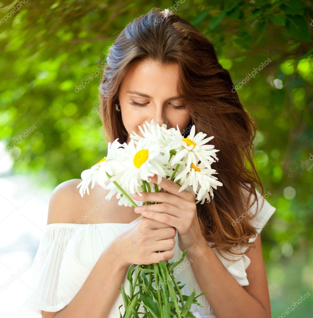Beautiful young woman smelling a bouquet of daisies, which in her hands. Close-up — Stock Photo #12274822