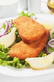 Breaded fish steaks with lemon and lettuce — Stock Photo