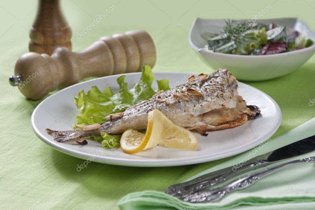 Baked sea bream with lettuce, lemon and parsley on the white plate — Stock Photo #11415512