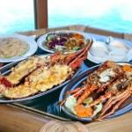 due piastre con aragosta sul tavolo alla finestra con vista sull'oceano — Foto Stock