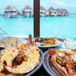 Two plates with lobster on table at window with view on ocean — Stockfoto