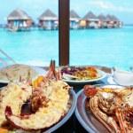 dwie płyty z homara w tabeli w oknie z widokiem na ocean — Zdjęcie stockowe