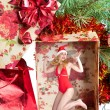 The girl in a New Year's cap in a gift box under a fir-tree — Stock Photo