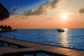 Island in ocean, overwater villas at the time sunset — Stock Photo