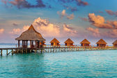 Villa on piles on water at the time sunset — Stock Photo