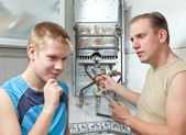The father and the son-teenager together in repair a gas water heater. — Stock Photo