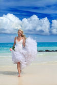 The young beautiful woman in a dress of the bride at edge of the sea with a rose in a hand — Stock Photo