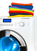 Pile of colorful clothes on the washing machine — Stock Photo