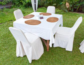Table with a white cloth and 4 chairs on a green lawn — Stock Photo