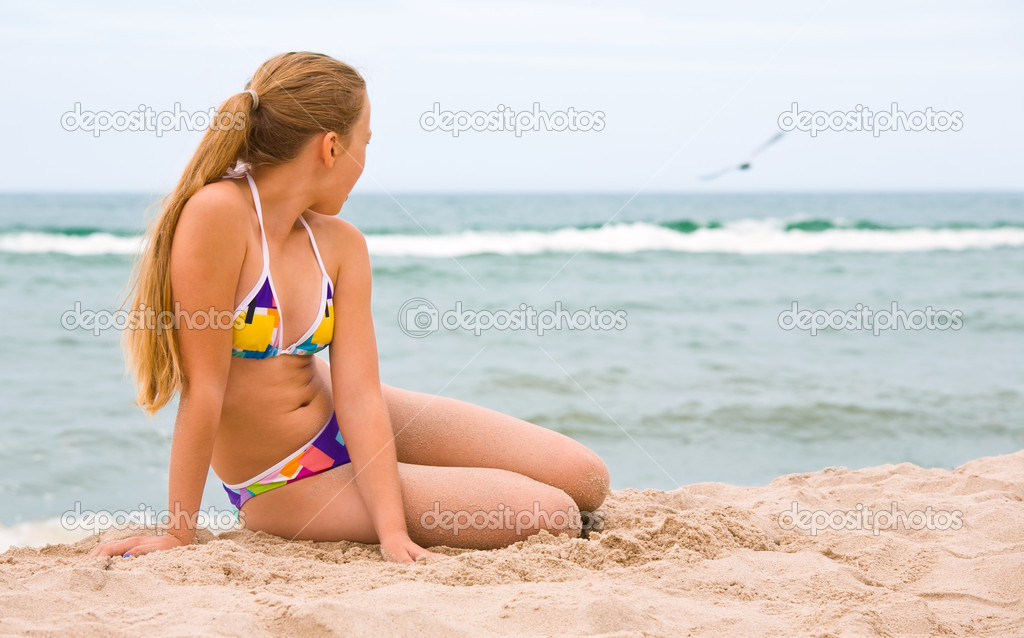 Young girl in swimsuit laying on the beach and looking at flying seagul — Stock Photo #12342364