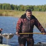 Постер, плакат: Smiling fisher with catch of fish