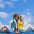 Blonde and brunette yong women on blue sky — Stock Photo #11835551