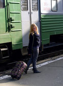 Girl with suitcase near train — Stock Photo