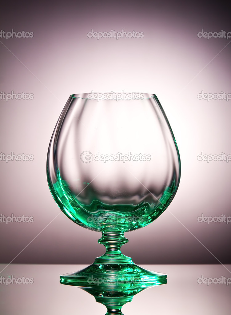 Empty cognac glass with a green tint on a shiny surface — Stock Photo #11899666