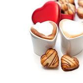 Heart shaped cream cookies on red heart metal box and coffee — Stock Photo