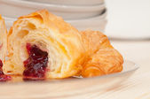 Croissant French brioche filled with berries jam — Stock Photo