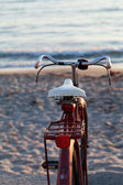 Old red bike on the beach — Stock Photo
