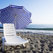 Chaise lounge with an umbrella standing alone on the bank of the blue sea — Stock Photo #11642440