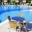 Table and chairs near a cool pool in a hot canicular day — Stock Photo