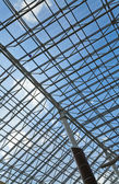 Glass roof of a modern building and blue sky — Stock Photo