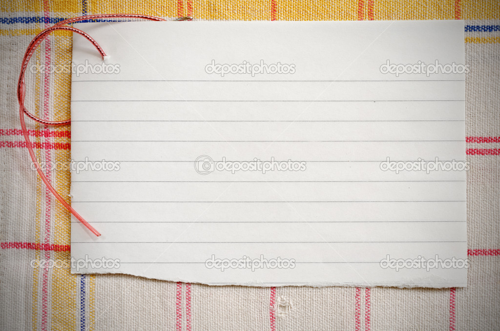 Torn lined paper with red wire on old tablecloth, vignetted horizontal shot — Stock Photo #10830134