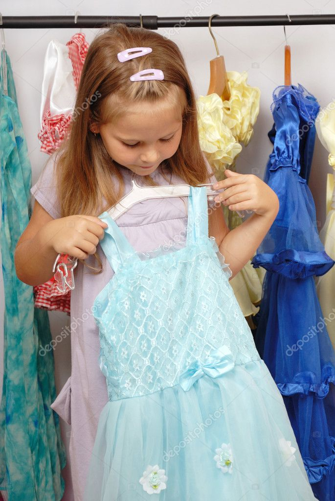 Little girl in shop of blue dresses  Stock Photo #11245990