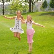 Two girls jump up barefoot in park under splash — Stock Photo