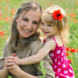 Mother and daughter in poppy field - Stock Photo