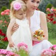 Mother and baby in rose garden — Stock Photo