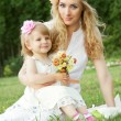 Mother and baby girl sitting on grass — Stockfoto