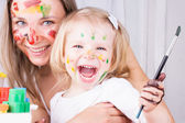 Happy mother and daughter painting — Stockfoto