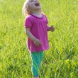 Joyful baby girl looking up in medow - Stock Photo