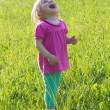 Stock Photo: Joyful baby girl looking up in medow