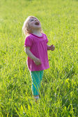 Joyful baby girl looking up in medow — Stock Photo