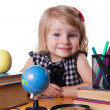 Girl sitting at table with books and globe - Stockfoto