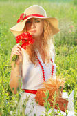 Woman in hat with poppy bouquet — Stock Photo