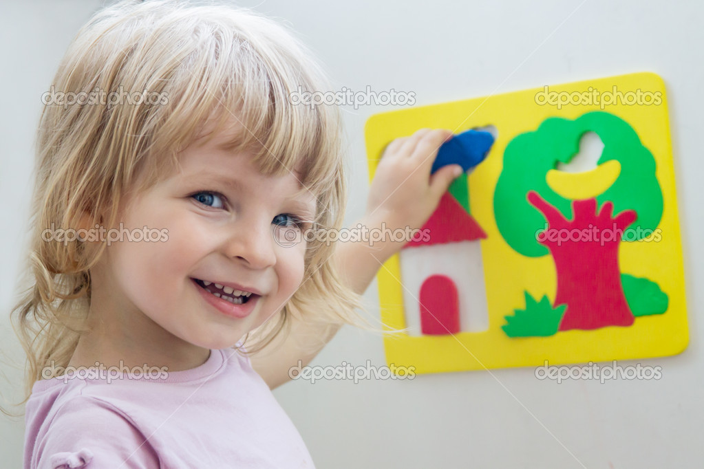 Happy girl playing soft constructor on light back — Stock Photo #11734777