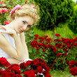Woman in white dress among rose garden — Stock Photo #11750594