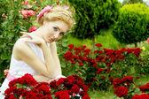 Frau im weißen kleid unter rosengarten — Stockfoto