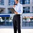 Businessman reading document outside a building — Stock Photo