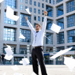 Young businessman throwing away his papers - Stock Photo
